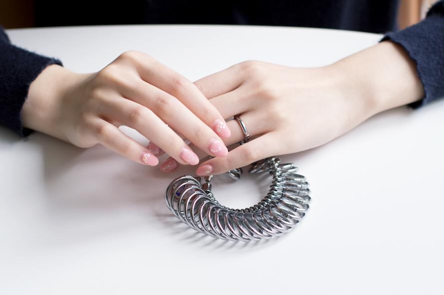 リングゲージでサイズを測る女性の手